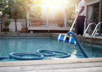 Man cleaning swimming pool with vacuum tube cleaner